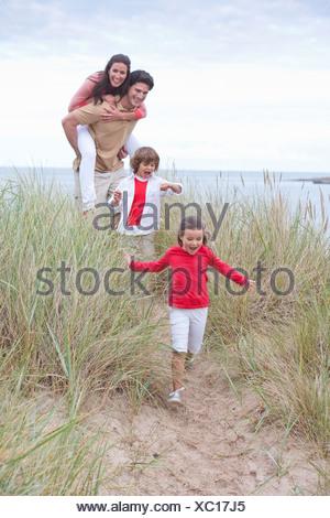 Balades en famille à travers les dunes sur la plage Banque D'Images