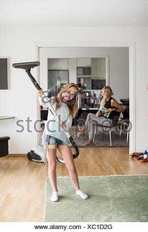 Full Length portrait of playful girl holding aspirateur à la maison avec la mère assis en arrière-plan Banque D'Images