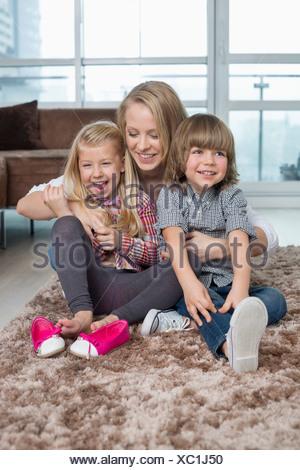 Mère ludique avec des enfants assis sur un tapis dans la salle de séjour Banque D'Images