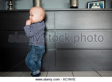Baby Boy leaning on salon bahut Banque D'Images