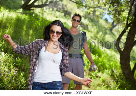 Smiling couple walking in woodlands Banque D'Images