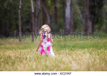 Vue arrière d'une fille marchant dans un champ portant un ours en peluche, Californie, États-Unis Banque D'Images