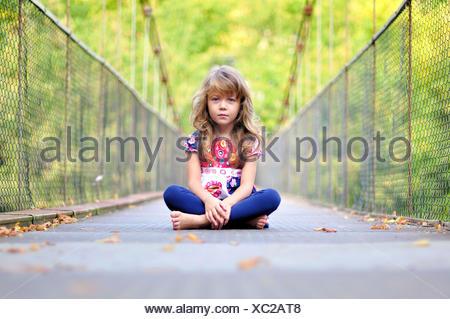 Portrait d'une petite fille assise sur un pont Banque D'Images