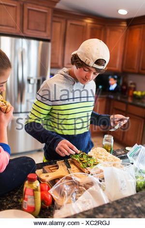 Frère et soeur dans la cuisine préparer sandwich Banque D'Images