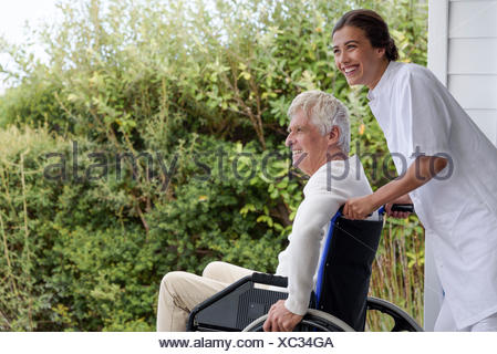 Infirmière aider senior man in wheelchair on porch Banque D'Images