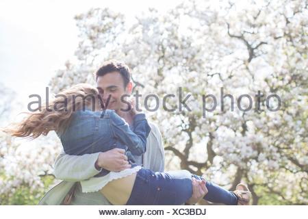 Homme Femme de levage en vertu de l'arbre avec des fleurs blanches Banque D'Images