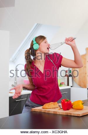 Femme chantant avec cuisine en fouettant Banque D'Images