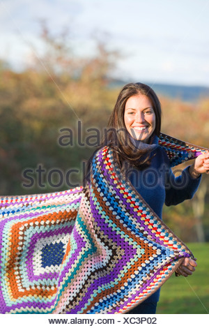Smiling woman wrapped in blanket outdoors Banque D'Images