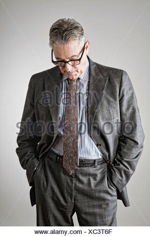 Senior man with hands in pockets, regardant vers le bas Banque D'Images