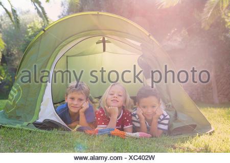 Portrait de trois enfants se trouvant dans une tente de jardin Banque D'Images