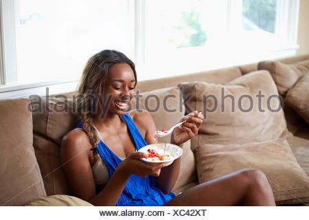 Jeune Femme prenant une pause formation, manger des fruits sur canapé Banque D'Images