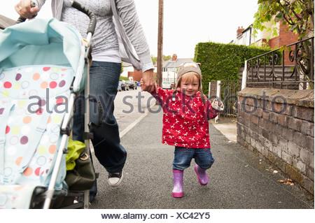 Bébé fille marcher avec la mère Banque D'Images