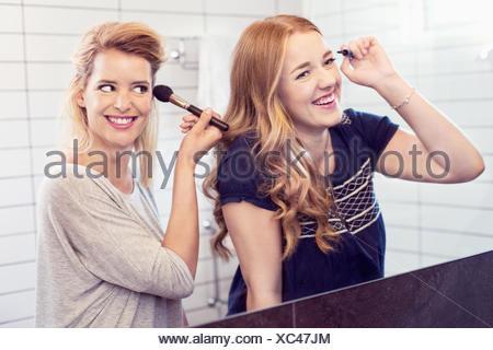 Heureux les jeunes sœurs appliquant le maquillage dans le rétroviseur Banque D'Images