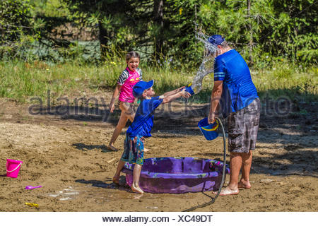 Les enfants et adultes dans une lutte , l'eau playfull sur un jour d'été chaud et ensoleillé. Cranbrook, Colombie-Britannique, Canada. Banque D'Images