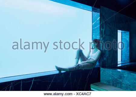 Femme assise sur le rebord de la vitre et regardant sous-vue de piscine Banque D'Images