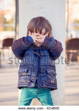 Petit garçon couvrant le visage avec ses mains Banque D'Images