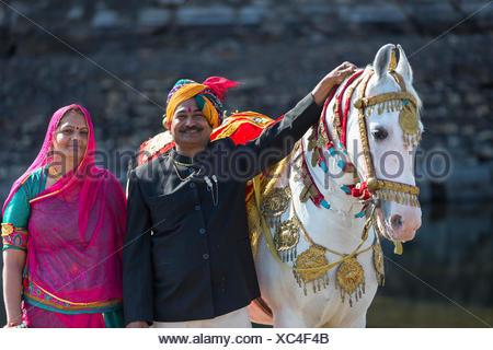 Chevaux Marwari. Cheval blanc dominant recouverts d'or, d'argent et de bijoux avec ses fiers propriétaires. Le Rajasthan, Inde Banque D'Images