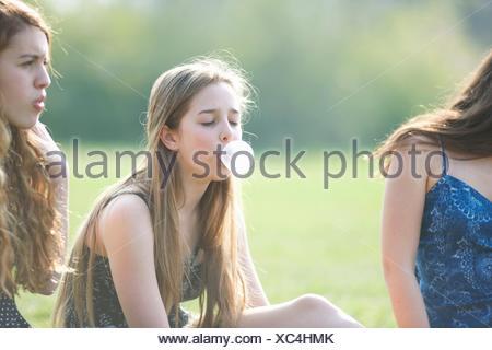 Woman blowing bubble gum bubble in park Banque D'Images