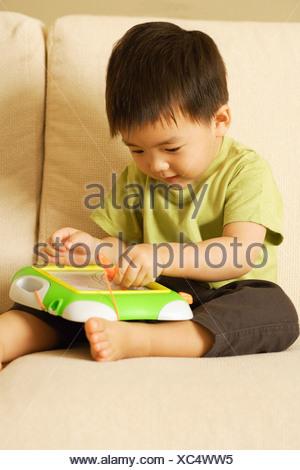Jeune garçon avec jouet sur canapé Banque D'Images