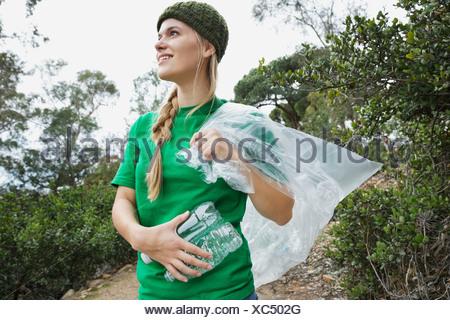 Vue latérale du magnifique jeune écologiste avec bouteilles d'eau vides et sac en plastique dans park Banque D'Images