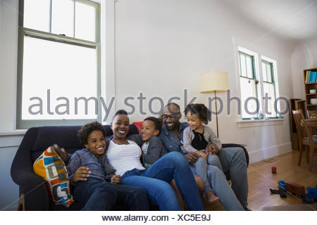 Le rire de la famille salon canapé Banque D'Images