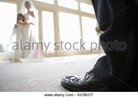 Mariée de demoiselle d'à côté et faire place au fenêtre, se concentrer sur la chaussure du marié en premier plan, close-up au niveau de la surface Banque D'Images