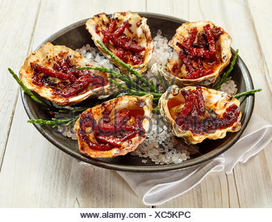 Angle de vue de la vie toujours élevé d'assiette d'Huîtres Kilpatrick préparé avec du bacon et du fromage et servi sur table en bois peint en blanc avec des draps serviette Banque D'Images