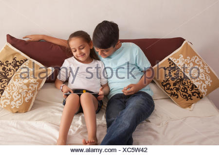 Brother and sister using digital tablet in bedroom Banque D'Images