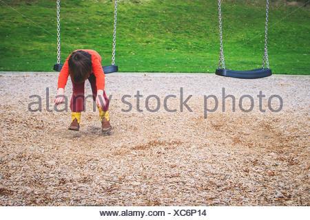 Garçon accroché sur une balançoire dans un jeu pour enfants Banque D'Images