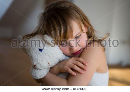 Jeune fille en détresse la maintenant sur ours Banque D'Images
