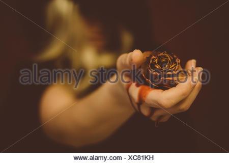 Portrait of Woman Holding Rose morte avec purge Banque D'Images