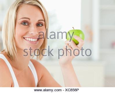 Jeune femme tenant une pomme verte à la caméra en Banque D'Images