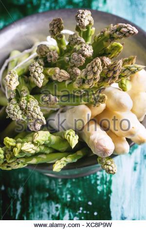 Groupe de jeunes asperges vertes et blanches en métal vintage bol sur table en bois vert. Vue d'en haut Banque D'Images