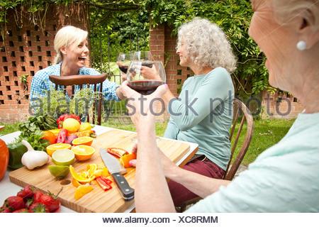 Les femmes qui élèvent trois générations d'un verre de vin rouge tout en préparant la nourriture à table de jardin Banque D'Images