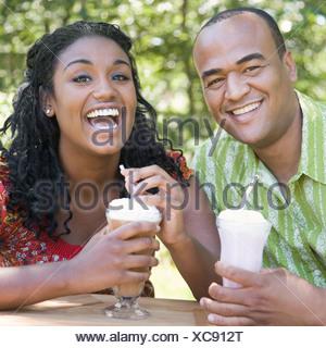 Portrait of a young man drinking milk-shake avec une jeune femme Banque D'Images