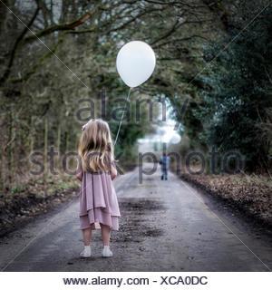 Vue arrière du girl holding a balloon regardant garçon courir loin de son Banque D'Images