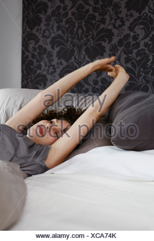 Young woman Lying in Bed stretching Banque D'Images
