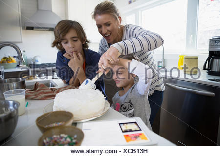 Family baking cake in kitchen Banque D'Images