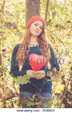 Teenage girl with heart shaped balloon appuyée à un arbre Banque D'Images