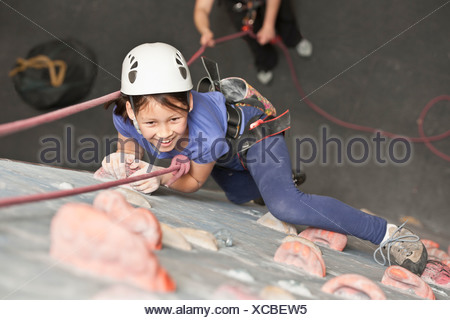 Girl climbing indoor rock wall Banque D'Images