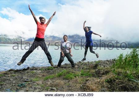 L'Indonésie, Nusa Tenggara Ouest, Mataram, Mont Rinjani, cheerful women jumping by lake Banque D'Images