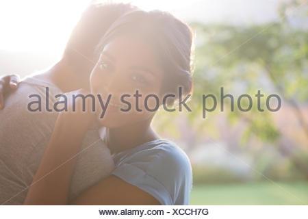 Portrait of smiling woman hugging man outdoors Banque D'Images