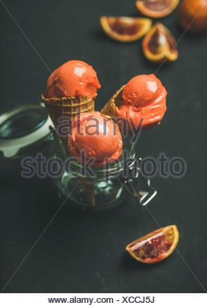Orange sanguine d'été rafraîchissante glace ou d'un sorbet boules à cônes alvéolés doux dans un bocal en verre, fond sombre, selective focus, composition verticale