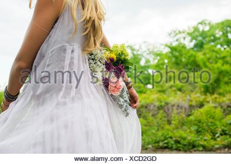 Cropped shot of young woman wearing white dress exerçant son bouquet de fleurs derrière son dos Banque D'Images