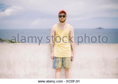 Portrait of young man standing in front of sea wall, San Pablo, Brésil Banque D'Images