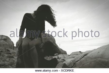 Femme assise sur des rochers contre Sky Banque D'Images