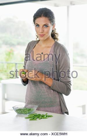 Woman peeling les pois verts dans la cuisine Banque D'Images