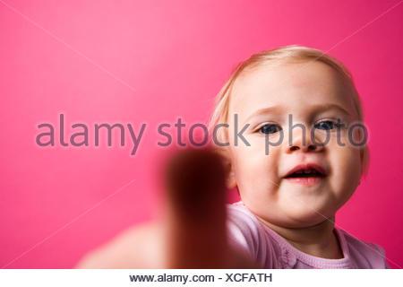 Portrait of a cute little girl essayer de toucher l'appareil Oceanside en Californie. Banque D'Images