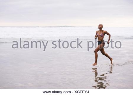 Woman in bikini jogging on beach Banque D'Images