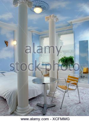 S chambres interiwith fausses colonnes blanches, table et chaises en métal, les murs et le plafond nuageux bleu, rose en marbre, deux blanches. Banque D'Images